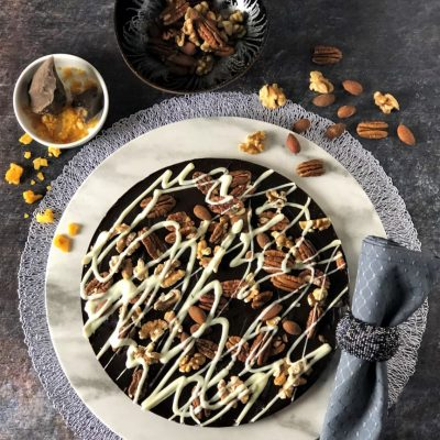 dark chocolate pizza with pecans almonds walnuts on white plate