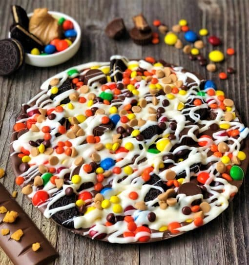 chocolate pizza peanut butter candies on wood planks