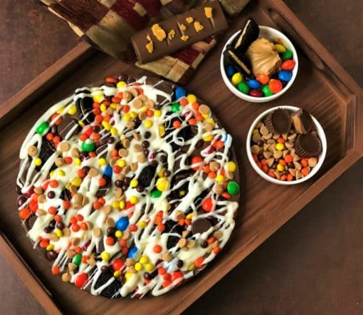 peanut butter avalanche chocolate pizza on wooden tray