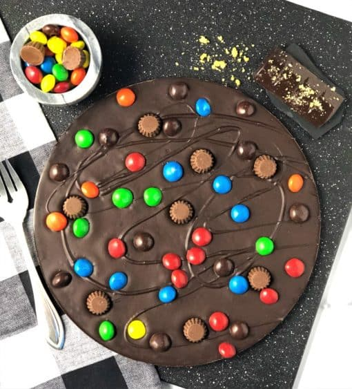 peanut butter cups and candies on dark chocolate pizza
