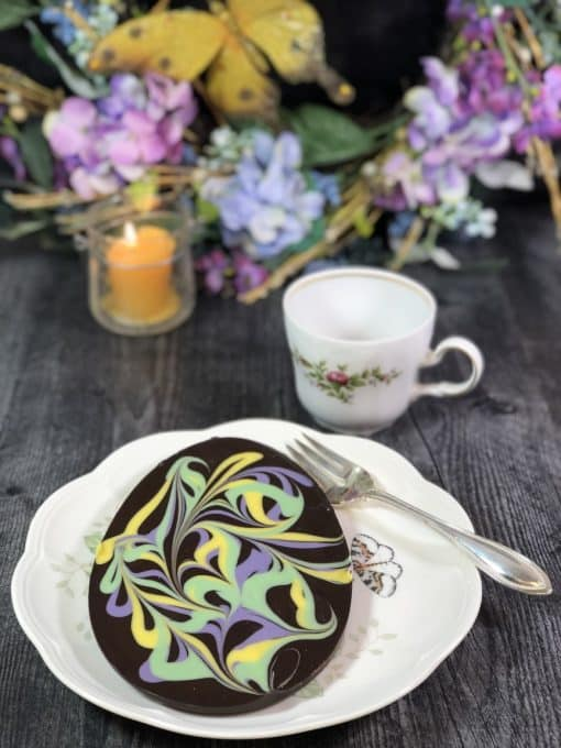 dark chocolate Easter egg with pastel swirls on table setting