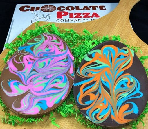 two chocolate Easter eggs with pastel colors on a board