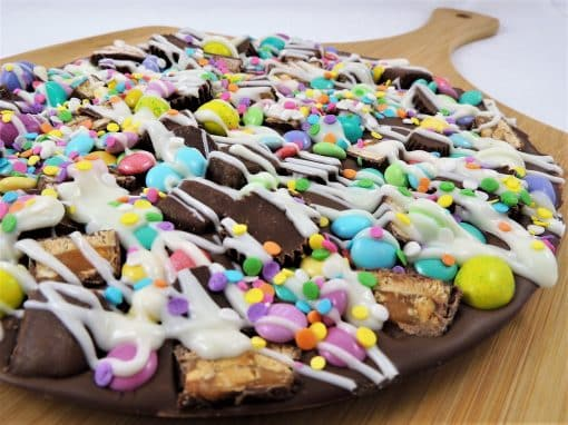 Gourmet Chocolate Pizza decorated in pastel chocolate candy peanut butter cups and served in a pizza box