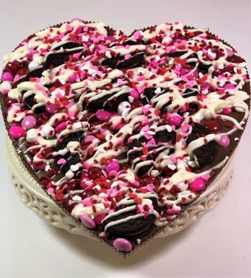 heart chocolate pizza topped with cookies and candy