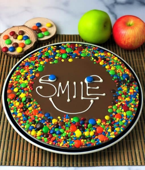 chocolate pizza with word smile on it and colorful candy border