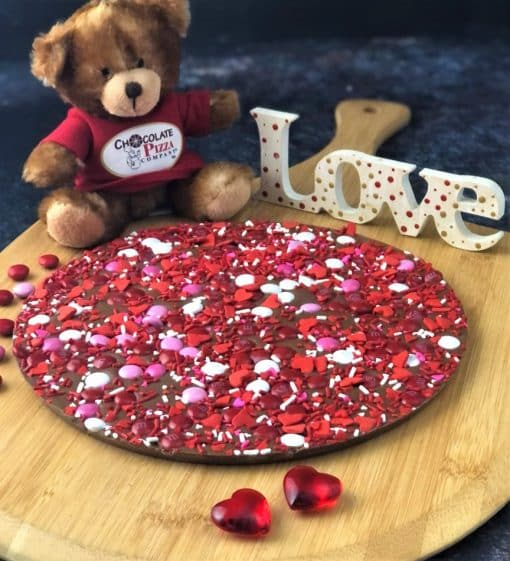 chocolate pizza with red candies on a wooden serving board
